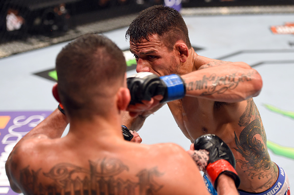 (R-L) Rafael dos Anjos of Brazil punches Anthony Pettis in their championship bout during the UFC 185 event on March 14, 2015 in Dallas. (Photo by Josh Hedges/Zuffa LLC)