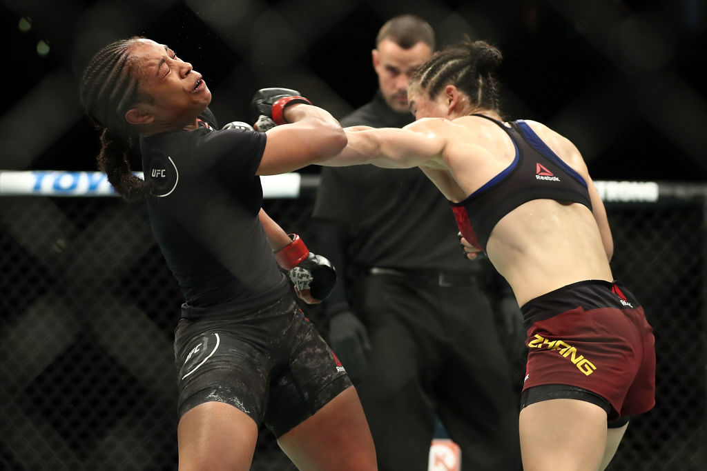LOS ANGELES, CA - AUGUST 04: Weili Zhang punches Danielle Taylor in the third round of the women's featherweight bout during UFC 227 at Staples Center on August 4, 2018 in Los Angeles, United States. (Photo by Joe Scarnici/Getty Images)