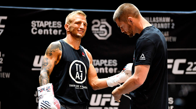 LOS ANGELES, CA - AUGUST 01:  (R-L) Coach Duane Ludwig laces the gloves of UFC bantamweight champion TJ Dillashaw during an open workout for fans and media at The Novo at LA Live on August 1, 2018 in Los Angeles, California. (Photo by Jeff Bottari/Zuffa LLC via Getty Images)