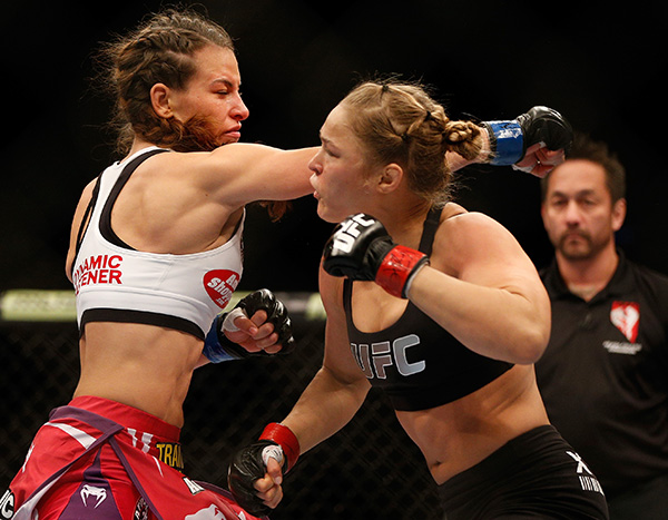 (L-R) Miesha Tate punches Ronda Rousey in their UFC women's bantamweight championship bout during UFC 168 event at the MGM Grand Garden Arena on December 28, 2013 in Las Vegas, Nevada. (Photo by Josh Hedges/Zuffa LLC)