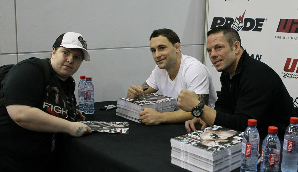 UFC Lightweight Champion Frankie Edgar (center) and UFC Welterweight fighter Marcus Davis (R) pose for a photo with a fan