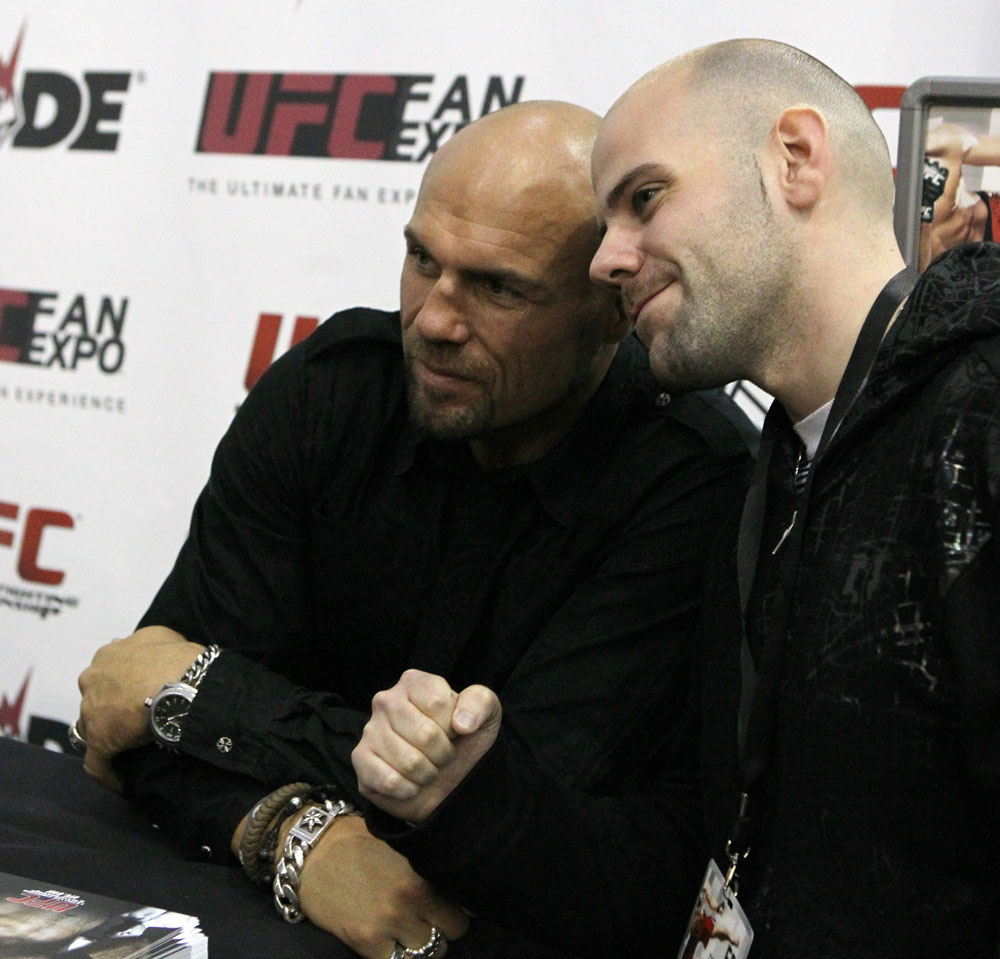 UFC Hall of Famer Randy &quot;The Natural&quot; Couture poses for a photo with a fan at the UFC Fan Expo London at Earl&#39;s Court