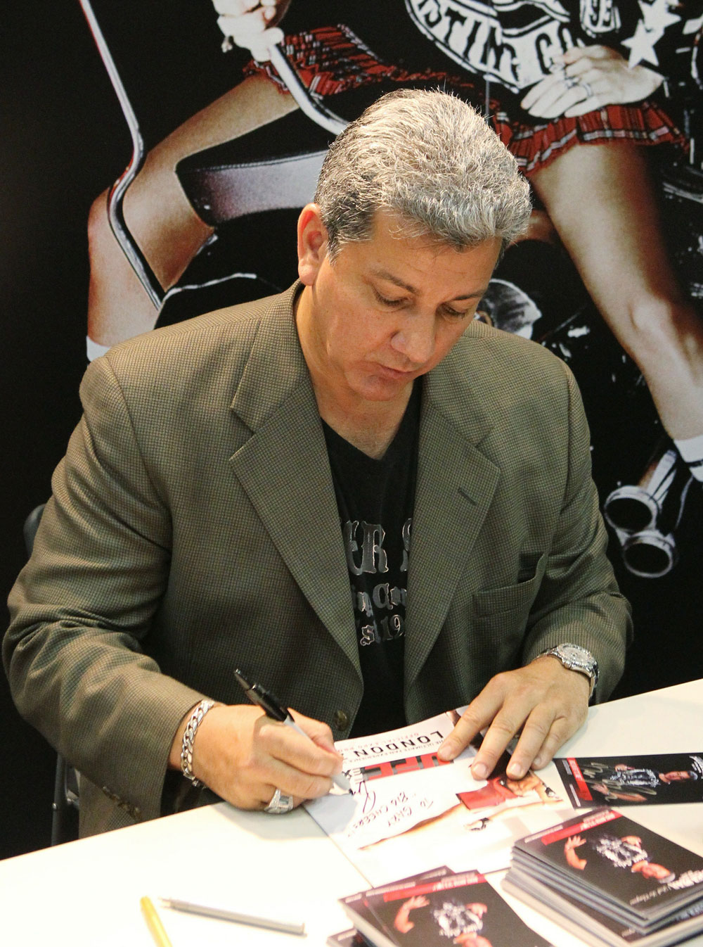 UFC announces Bruce Buffer signs an autograph for a fan.
