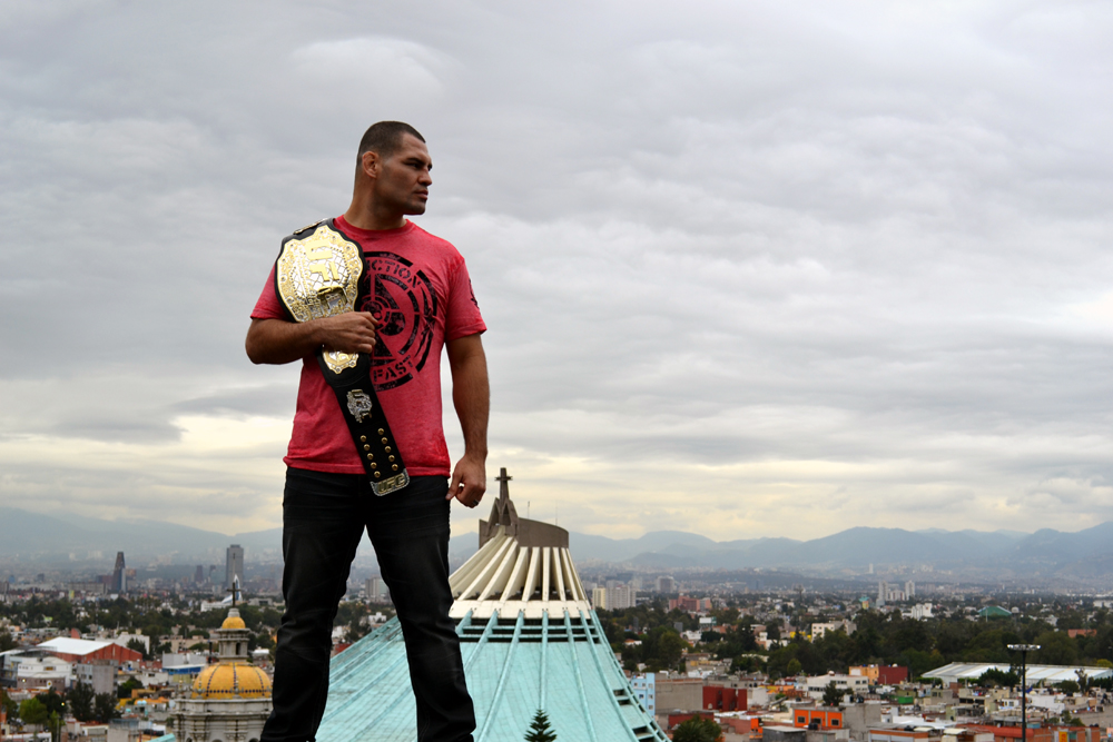 "Velasquez posses with his belt in front of ""La Villa"", home of ""La Vigen de Guadalupe"", the most important religious icon in Mexico. (Juan Cardenas/Zuffa LLC)"