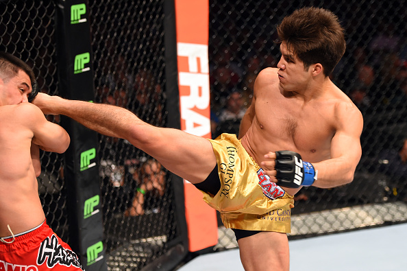 DALLAS, TX - MARCH 14:  (R-L) Henry Cejudo kicks the head of <a href='../fighter/Chris-Cariaso'>Chris Cariaso</a> in their flyweight bout during the UFC 185 event at the American Airlines Center on March 14, 2015 in Dallas, Texas. (Photo by Josh Hedges/Zuffa LLC/Zuffa LLC)