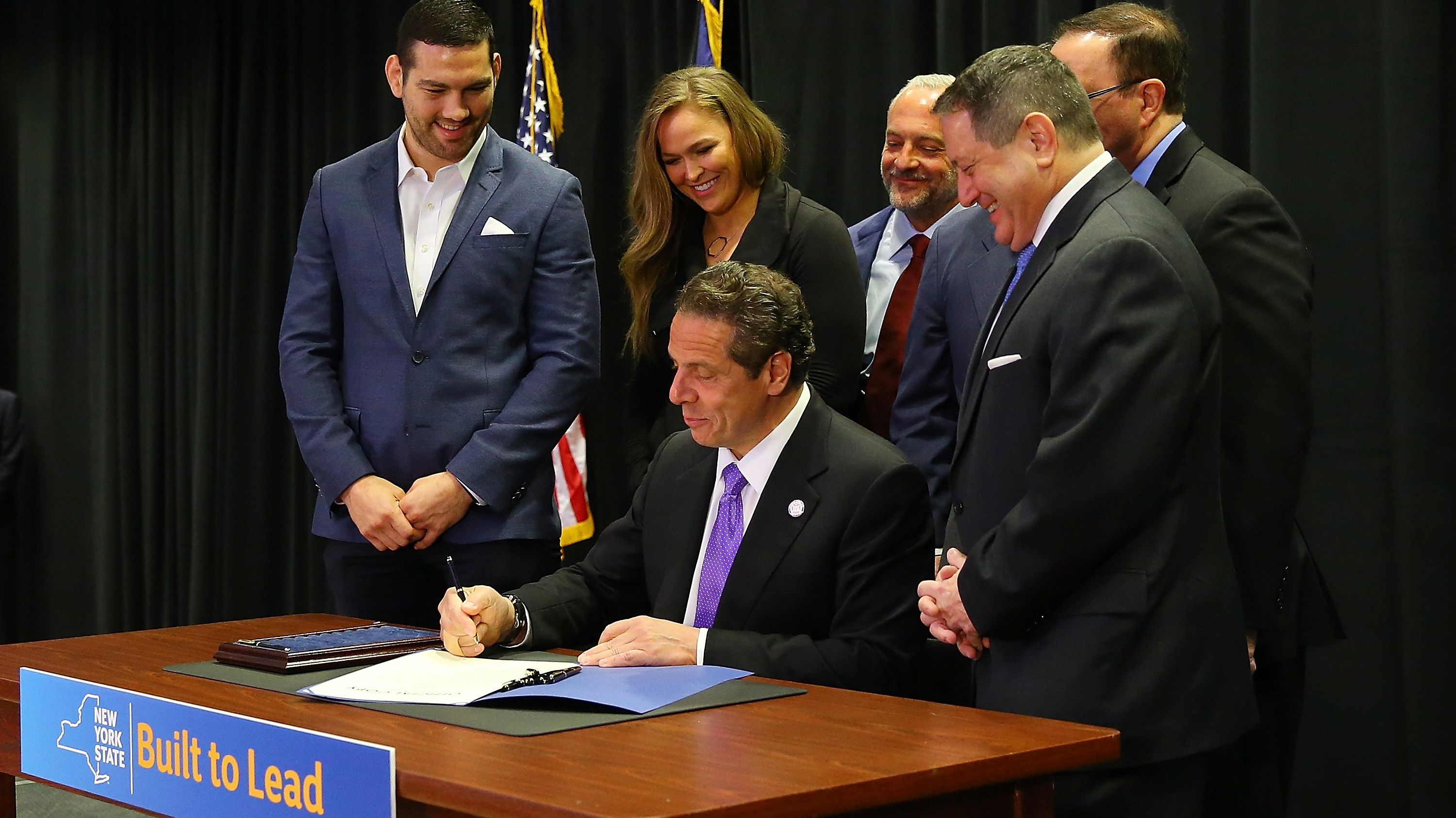New York Governor Andrew Cuomo is joined by (from left) UFC fighters Chris Weidman and Ronda Rousey, UFC CEO Lorenzo Fertitta, Madison Square Garden President James Dolan, Senator Joe Griffo and Assemblyman Joseph Morelle as he signs a bill to legalize Mixed Martial Arts fighting in the state during a ceremony at Madison Square Garden on April 14, 2016 in New York City. (Photo by Mike Stobe/Zuffa LLC/Zuffa LLC via Getty Images)