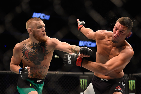Conor McGregor punches Nate Diaz during their rematch at UFC 202