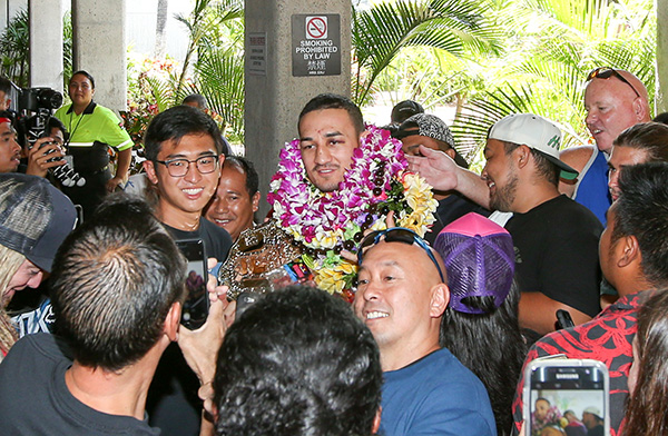 Max Holloway (center) is surrounded by fans after arriving at the Daniel K. Inouye International Airport on June 5, 2017 in Honolulu, Hawaii. Holloway became the the undisputed UFC Featherweight Champion after beating Jose Aldo. (Photo by Zuffa LLC)