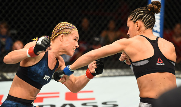<a href='../fighter/Felice-Herrig'>Felice Herrig</a> and <a href='../fighter/cortney-casey'>Cortney Casey</a> exchange punches in their women's strawweight bout during the UFC 218 event inside Little Caesars Arena on December 02, 2017 in Detroit, Michigan. (Photo by Josh Hedges/Zuffa LLC)