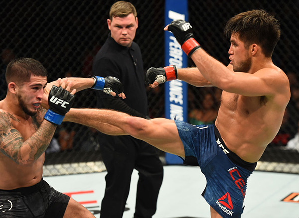 Henry Cejudo kicks Sergio Pettis in their flyweight bout during the UFC 218 event inside Little Caesars Arena