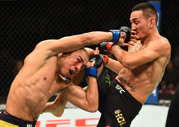 (R-L) &lt;a href='../fighter/Max-Holloway'&gt;<a href='../fighter/Max-Holloway'>Max Holloway</a>&lt;/a&gt; lands a knee against &lt;a href='../fighter/Jose-Aldo'&gt;<a href='../fighter/Jose-Aldo'>Jose Aldo</a>&lt;/a&gt; of Brazil in their UFC featherweight championship bout during the UFC 218 event inside Little Caesars Arena on December 02, 2017 in Detroit, Michigan. (Photo by Josh Hedges/Zuffa LLC)