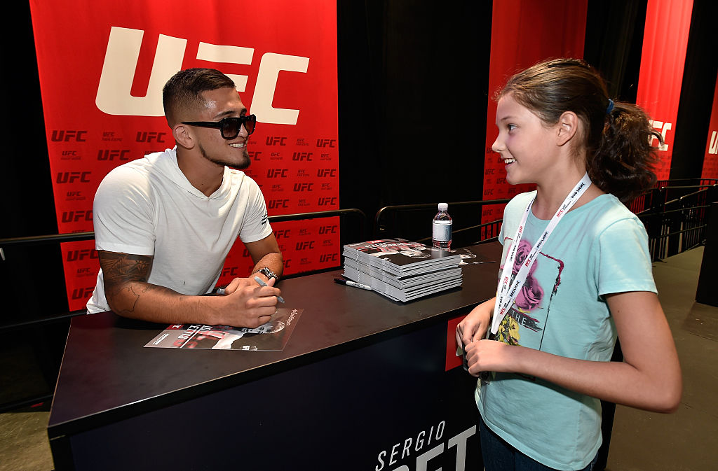 LAS VEGAS, NV - JULY 08:  Mixed martial artist Sergio Pettis (L) meets with a young fan at the UFC Fan Expo at the Las Vegas Convention Center on July 8, 2016 in Las Vegas, Nevada.  (Photo by David Becker/Zuffa LLC)
