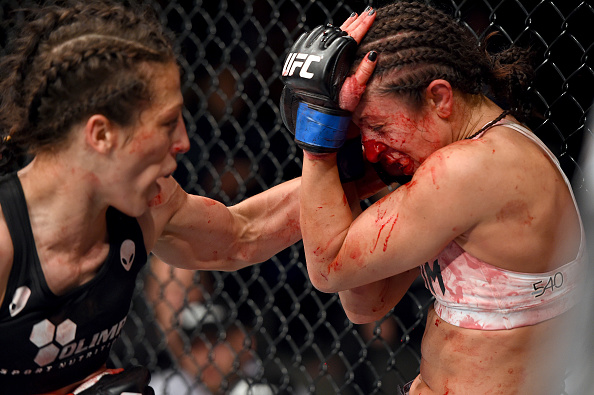(L-R) Joanna Jedrzejczyk of Poland punches Jessica Penne of the United States in their women's strawweight championship bout during the UFC Fight Night event at the O2 World on June 20, 2015 in Berlin, Germany. (Photo by Josh Hedges/Zuffa LLC)