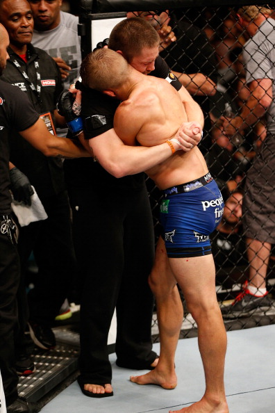 TJ Dillashaw embraces trainer Duane Ludwig after defeating Renan Barao. (Photo by Josh Hedges/Zuffa LLC)