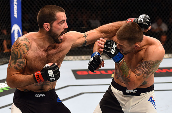Matt Brown punches <a href='../fighter/Tim-Means'>Tim Means</a> in their welterweight fight during the UFC 189 event inside MGM Grand Garden Arena on July 11, 2015 in Las Vegas, Nevada. (Photo by Josh Hedges/Zuffa LLC)