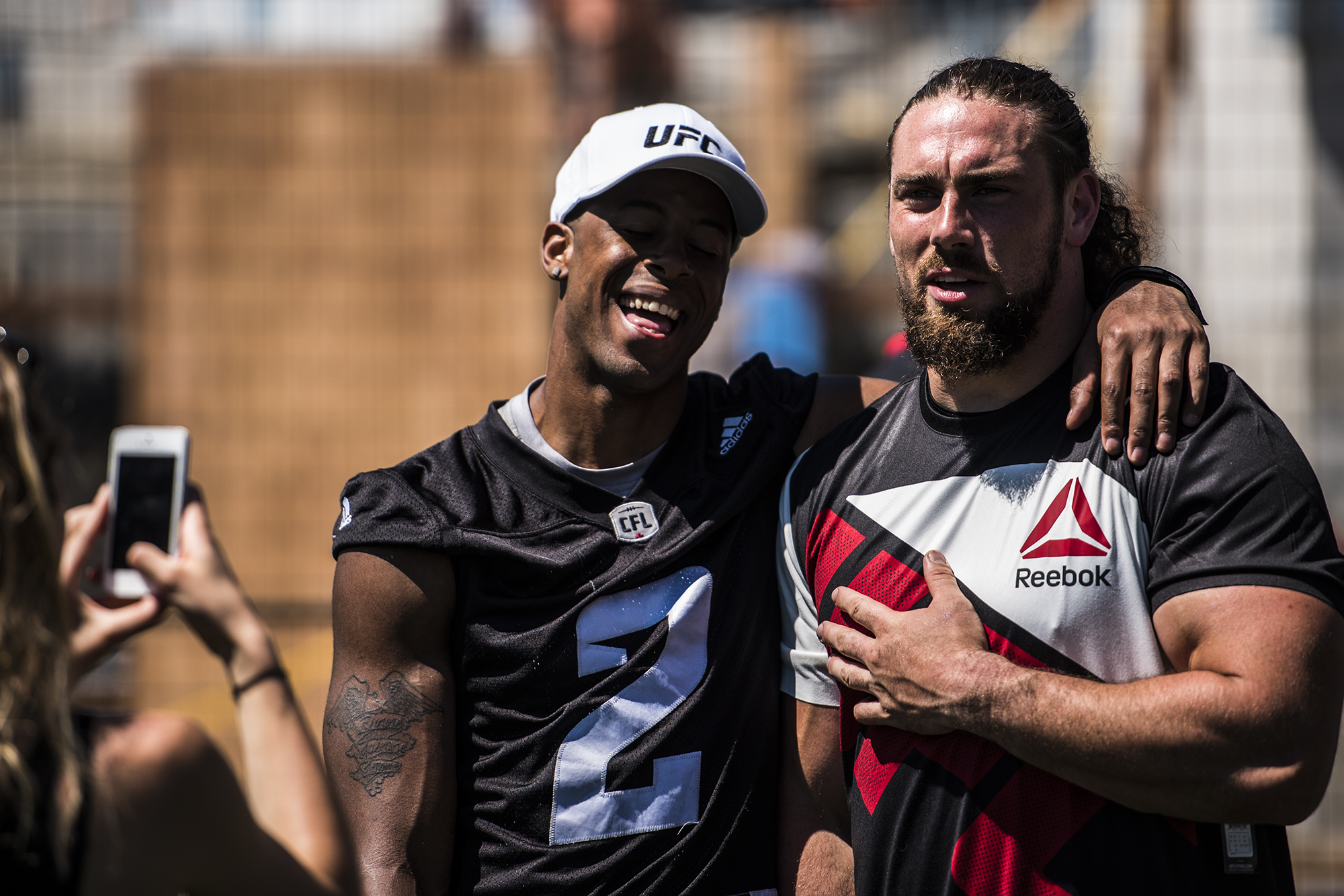 Jermaine Robinson (left) and Connor Williams (right) watch as UFC fighters Cowboy Cerrone and Misha Turkunov demonstrate proper MMA technique at Redblacks practice Wednesday afternoon. (John Barry/ Zuffa LLC)