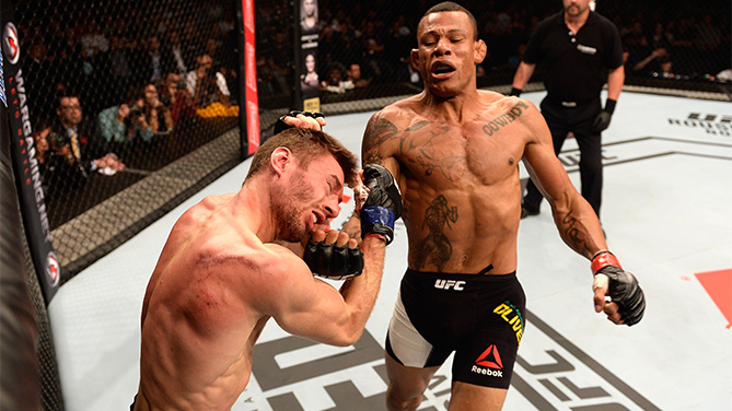 Alex Oliveira of Brazil punches Piotr Hallmann of Poland in their lightweight bout during the UFC Fight Night Belfort v Henderson at Ibirapuera Gymnasium on November 7, 2015 in Sao Paulo, Brazil.  (Photo by Buda Mendes/Zuffa LLC)