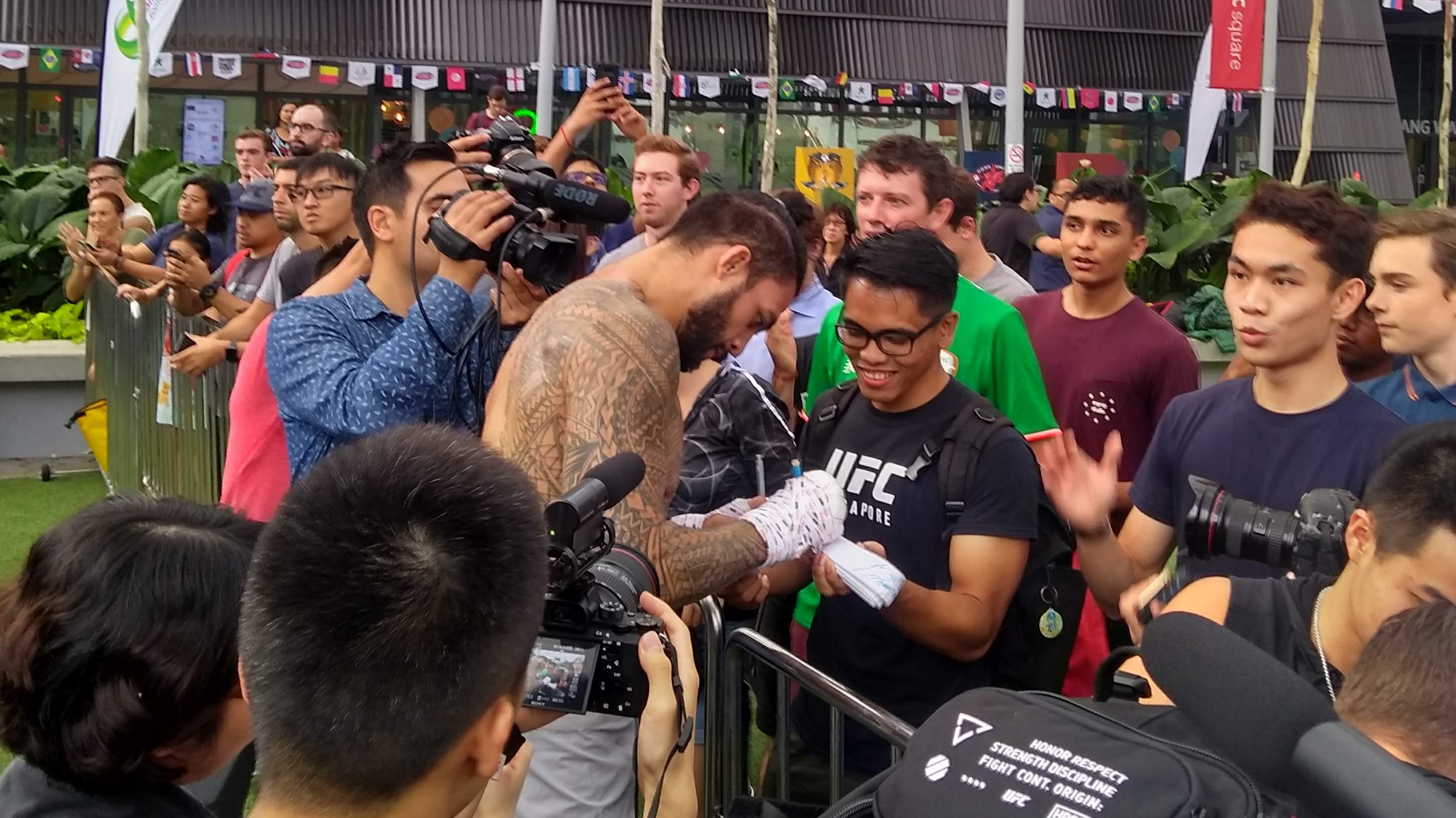 <a href='../fighter/tyson-pedro'>Tyson Pedro</a> signs autographs for fans following his open workout for Fight Night Singapore on 6/20/18 (Photo by Steve Latrell/Zuffa LLC)