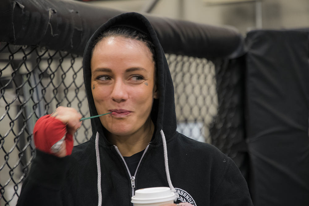 Jessica-Rose Clark smiles and finishes a coffee inside the cage at Syndicate MMA before her last training session before going to St. Louis.
