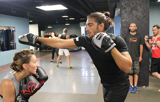 VANCOUVER, BC - AUG. 25 - (Right) Elias Theodorou throws a hook while holding mitts for Katie Cassidy (left) who ducks during a training session at In Fitness martial arts gym. (Photo by Matt Parrino/Zuffa LLC).