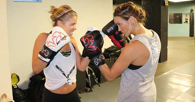 VANCOUVER, BC - Aug. 25: (Left) Emily Bett Rickards and Katie Cassidy, stars of the hit television series Arrow on The CW, have a face off before training with UFC stars Stephen