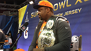 UFC correspondent Megan Olivi and featherweight contender Ricardo Lamas show off the UFC championship belt to various NFL stars from the Seattle Seahawks and Denver Broncos at the Super Bowl media day.