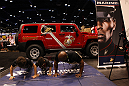 Two young fans do push-ups with at Marine at the United States Marine Corps booth at the UFC Fan Expo