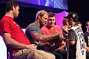 Josh Koscheck signs an autograph for a young fan during a Q&A session at the UFC Fan Expo