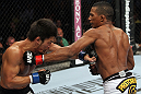 RIO DE JANEIRO, BRAZIL - JANUARY 14:  Yuri Alcantara (R) punches Michihiro Omigawa (L) in a featherweight bout during UFC 142 at HSBC Arena on January 14, 2012 in Rio de Janeiro, Brazil.  (Photo by Josh Hedges/Zuffa LLC/Zuffa LLC via Getty Images)