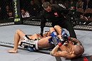 LAS VEGAS, NV - FEBRUARY 04:  Dustin Poirier (right) attempts to submit Max Holloway as referee Steve Mazzagatti looks on during the UFC 143 event at Mandalay Bay Events Center on February 4, 2012 in Las Vegas, Nevada.  (Photo by Nick Laham/Zuffa LLC/Zuffa LLC via Getty Images) *** Local Caption *** Dustin Poirier; Steve Mazzagatti