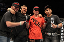 OMAHA, NE - FEBRUARY 15:  TJ Dillashaw (orange shirt) poses for a photo with his team after defeating Walel Watson during the UFC on FUEL TV event at Omaha Civic Auditorium on February 15, 2012 in Omaha, Nebraska.  (Photo by Josh Hedges/Zuffa LLC/Zuffa LLC via Getty Images) *** Local Caption *** TJ Dillashaw; Urijah Faber
