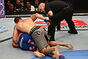 SAN JOSE, CA - JULY 11:   Chris Weidman (grey shorts) punches Mark Munoz (blue shorts) as referee Josh Rosenthal during their middleweight bout at HP Pavilion on July 11, 2012 in San Jose, California.  (Photo by Ezra Shaw/Zuffa LLC/Zuffa LLC via Getty Images)  *** Local Caption *** Mark Munoz; Chris Weidman; Josh Rosenthal