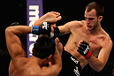 LOS ANGELES, CA - AUGUST 04:  Cole Miller (R) kicks Nam Phan in their featherweight bout during UFC on FOX at Staples Center on August 4, 2012 in Los Angeles, California.  Phan defeated Miller by split decision.  (Photo by Josh Hedges/Zuffa LLC via Getty Images)