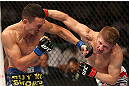 DENVER, CO - AUGUST 11:  (L-R) Max Holloway and Justin Lawrence trade punches during their featherweight bout at UFC 150 inside Pepsi Center on August 11, 2012 in Denver, Colorado. (Photo by Nick Laham/Zuffa LLC/Zuffa LLC via Getty Images)