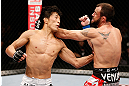 MACAU, MACAU - NOVEMBER 10:  (L-R) Takeya Mizugaki punches Jeff Hougland during their bantamweight bout at the UFC Macao event inside CotaiArena on November 10, 2012 in Macau, Macau.  (Photo by Josh Hedges/Zuffa LLC/Zuffa LLC via Getty Images)