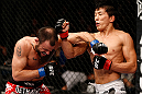 MACAU, MACAU - NOVEMBER 10:  (R-L) Takeya Mizugaki punches Jeff Hougland during their bantamweight bout at the UFC Macao event inside CotaiArena on November 10, 2012 in Macau, Macau.  (Photo by Josh Hedges/Zuffa LLC/Zuffa LLC via Getty Images)