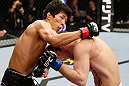 SAITAMA, JAPAN - MARCH 03:  (L-R) Takeya Mizugaki punches Bryan Caraway in their bantamweight fight during the UFC on FUEL TV event at Saitama Super Arena on March 3, 2013 in Saitama, Japan.  (Photo by Josh Hedges/Zuffa LLC/Zuffa LLC via Getty Images)