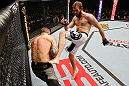 STOCKHOLM, SWEDEN - APRIL 06:  (R-L) Ryan Couture kicks Ross Pearson in their lightweight fight at the Ericsson Globe Arena on April 6, 2013 in Stockholm, Sweden.  (Photo by Josh Hedges/Zuffa LLC/Zuffa LLC via Getty Images)