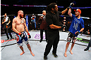 NEWARK, NJ - APRIL 27:  Referee Herb Dean (C) raises the arm of winner Pat Healy (R) after defeating Jim Miller (L) by Technical Submission (rear-naked choke) in their lightweight bout during the UFC 159 event at the Prudential Center on April 27, 2013 in Newark, New Jersey.  (Photo by Al Bello/Zuffa LLC/Zuffa LLC Via Getty Images)