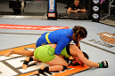 LAS VEGAS, NV - JUNE 6:  Julianna Pena (blue shorts) wrestles Shayna Baszler (green shorts) in their preliminary fight during filming of season eighteen of The Ultimate Fighter on June 6, 2013 in Las Vegas, Nevada. (Photo by Al Powers/Zuffa LLC/Zuffa LLC via Getty Images)
