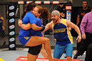 LAS VEGAS, NV - JUNE 6:  Coach Miesha Tate (C) and Team Tate trainer Brian Caraway (R) celebrate with Julianna Pena (L) after she submits Shayna Baszler (not pictured) in their preliminary fight during filming of season eighteen of The Ultimate Fighter on June 6, 2013 in Las Vegas, Nevada. (Photo by Al Powers/Zuffa LLC/Zuffa LLC via Getty Images)