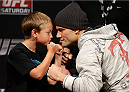 SACRAMENTO, CA - DECEMBER 13:  UFC lightweight contender Josh Thomson (R) poses for a photo with a young fan during a Q&A session before the UFC on FOX weigh-in at Sleep Train Arena on December 13, 2013 in Sacramento, California. (Photo by Josh Hedges/Zuffa LLC/Zuffa LLC via Getty Images)