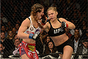LAS VEGAS, NV - DECEMBER 28:  (R-L) Ronda Rousey punches Miesha Tate in their UFC women's bantamweight championship bout during the UFC 168 event at the MGM Grand Garden Arena on December 28, 2013 in Las Vegas, Nevada. (Photo by Donald Miralle/Zuffa LLC/Zuffa LLC via Getty Images) *** Local Caption *** Ronda Rousey; Miesha Tate