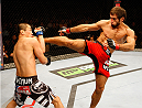 SINGAPORE - JANUARY 04:  Mairbek Taisumov goes for a kick on Bang Tae Hyun in their lightweight bout during the UFC Fight Night event at the Marina Bay Sands Resort on January 4, 2014 in Singapore. (Photo by Mitch Viquez/Zuffa LLC/Zuffa LLC via Getty Images)