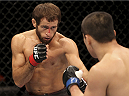 SINGAPORE - JANUARY 04:  (L to R) Mairbek Taisumov faces off with Bang Tae Hyun in their lightweight bout during the UFC Fight Night event at the Marina Bay Sands Resort on January 4, 2014 in Singapore. (Photo by Mitch Viquez/Zuffa LLC/Zuffa LLC via Getty Images)