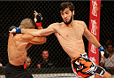 JARAGUA DO SUL, BRAZIL - FEBRUARY 15:  (R-L) Zubaira Tukhugov delivers a spinning back fist against Douglas Silva de Andrade in their featherweight fight during the UFC Fight Night event at Arena Jaragua on February 15, 2014 in Jaragua do Sul, Santa Catarina, Brazil. (Photo by Josh Hedges/Zuffa LLC/Zuffa LLC via Getty Images)