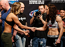 LAS VEGAS, NV - FEBRUARY 21:  (L-R) Opponents Ronda Rousey and Sara McMann shake hands during the UFC 170 weigh-in event at the Mandalay Bay Events Center on February 21, 2014 in Las Vegas, Nevada. (Photo by Josh Hedges/Zuffa LLC/Zuffa LLC via Getty Images)