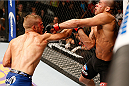 LAS VEGAS, NV - MAY 24:  (L-R) T.J. Dillashaw punches Renan Barao in their bantamweight championship bout during the UFC 173 event at the MGM Grand Garden Arena on May 24, 2014 in Las Vegas, Nevada. (Photo by Josh Hedges/Zuffa LLC/Zuffa LLC via Getty Images)