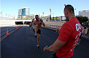 LAS VEGAS, NV - JULY 4:  A participate does his workout at the third station in the first annual Ulti-man 5K run during UFC International Fight Week at Hogs and Heifers on July 4, 2014 in Las Vegas, Nevada. Proceeds will help support Three Square Food Bank. (Photo by Brandon Magnus/Zuffa LLC/Zuffa LLC via Getty Images)