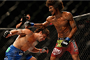 LAS VEGAS, NV - JULY 05:  (R-L) Alex Caceres and Urijah Faber trade punches in their bantamweight fight at UFC 175 inside the Mandalay Bay Events Center on July 5, 2014 in Las Vegas, Nevada.  (Photo by Josh Hedges/Zuffa LLC/Zuffa LLC via Getty Images)